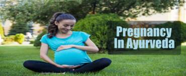 Pregnant lady sitting in garden with greenery trees